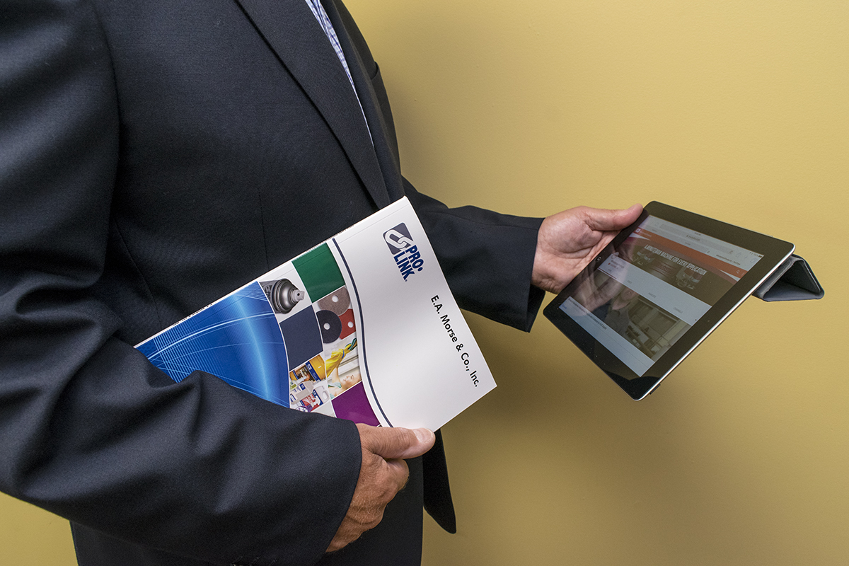 A man holds a tablet and product catalog.